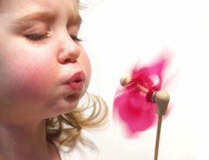 Девушка дует на пропеллер
