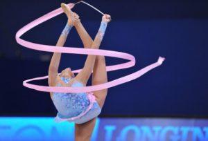 Гимнастка стоит на одной ноге