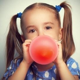 Девочка надувает шарик