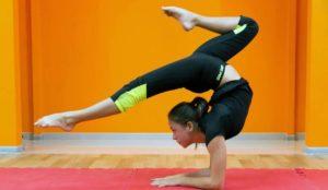 Спортсменка вверх ногами с упорой на руки