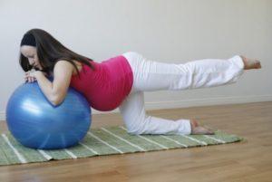 Девушка упирается на шар руками