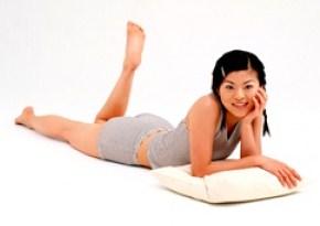 Лежа на животе девушка болтает ногами