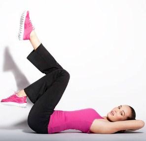 Девушка крутит ногами лежа на спине