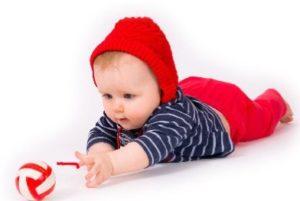 Малыш тянется за игрушкой